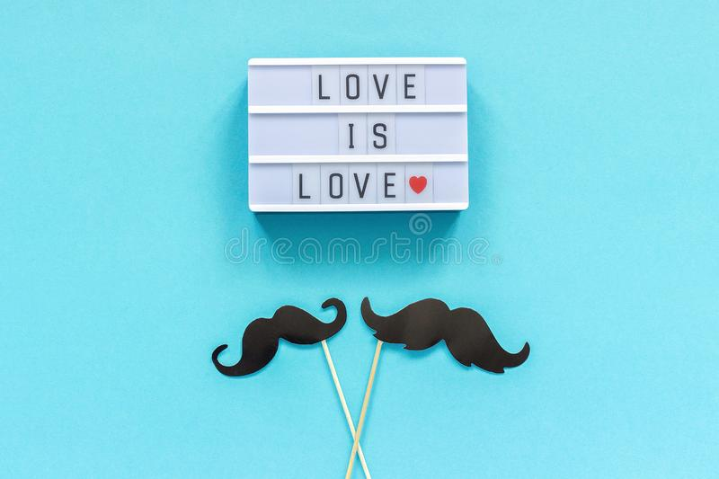 Couple paper mustache props on stick and light box with text Love is love on blue background. Concept Homosexuality gay love. Couple paper mustache props on stock images