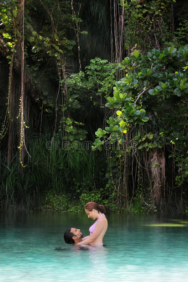 Couple in paradise. Young happy couple embracing in a secluded tropical paradise setting stock photos