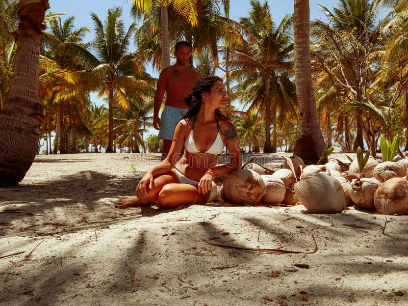 Lovely travel couple standing near coconut shells and palm trees in paradise Onok Island in Balabac Palawan in Philippines. Couple at the paradise with white royalty free stock photos