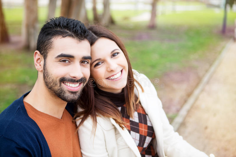 Couple in Park. Young romantic couple on a bench in park royalty free stock photos