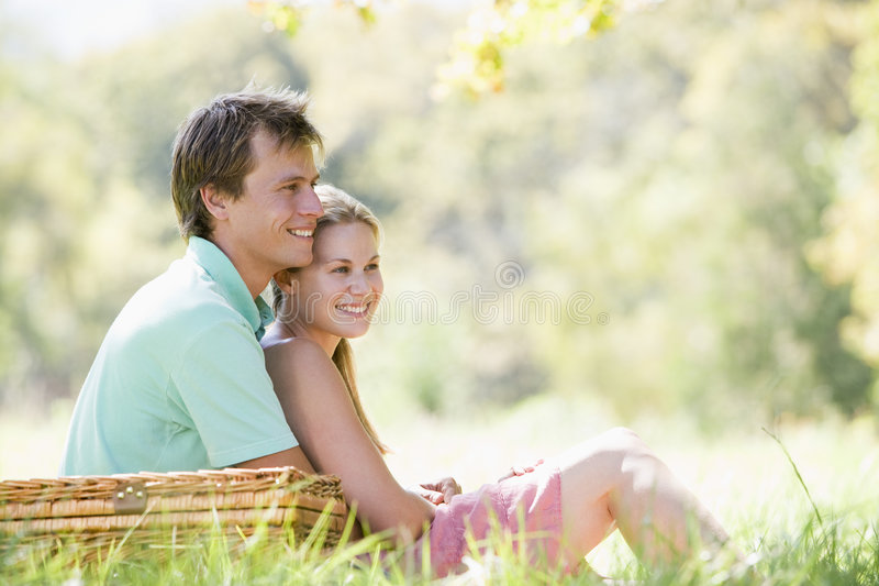 Couple at park having a picnic and smiling stock images