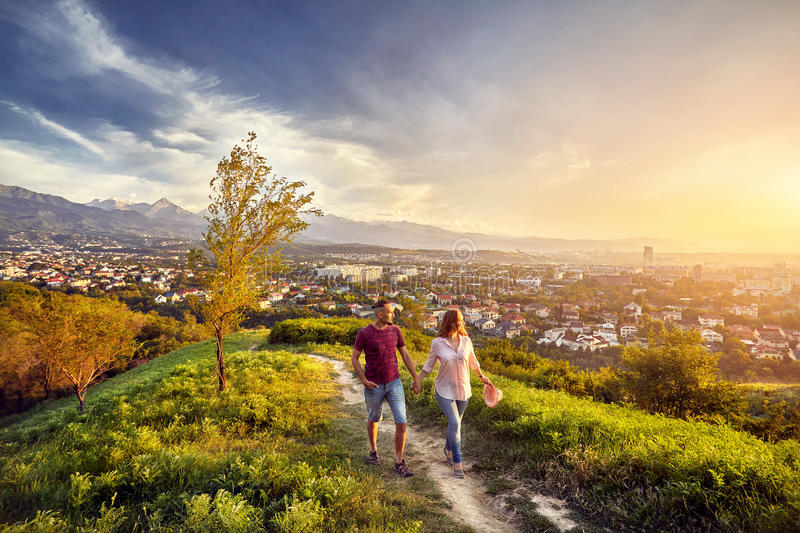 Couple in the park at sunset city view. Yong couple in pink clothes walking in the park at the sunset city view background stock photography