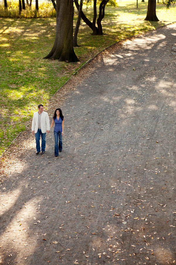 Couple Park Walk. A happy couple walking in the park on a sunny day royalty free stock photo