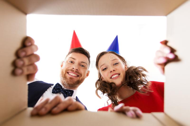 Couple in party hats opening birthday gift box. People, surprise and holidays concept - happy couple in party hats opening birthday gift box stock photo
