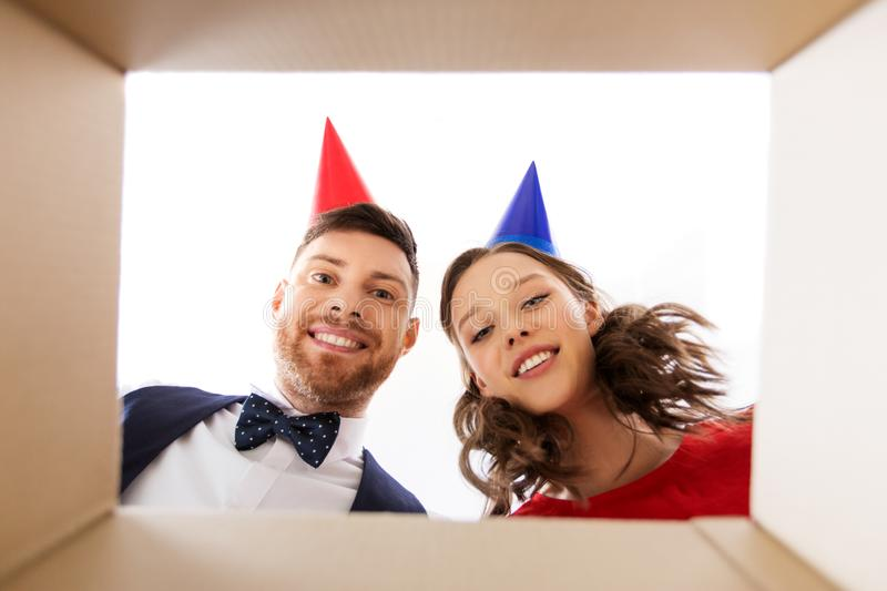 Couple in party hats opening birthday gift box. People, surprise and holidays concept - happy couple in party hats opening birthday gift box stock image