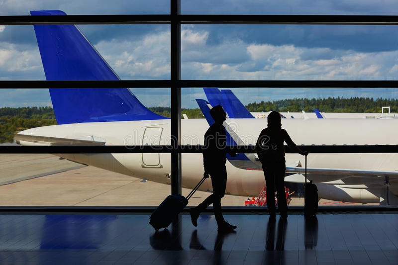 Couple of passengers in airport, looking through the window at planes stock images