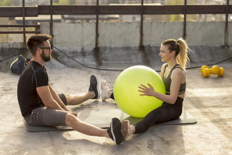 Couple passing the pilates ball. Couple sitting on a yoga mat on a building rooftop terrace, exercising with a pilates ball stock photos