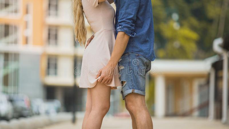 Couple passionately embracing in city street, tender relationship, safe sex stock images