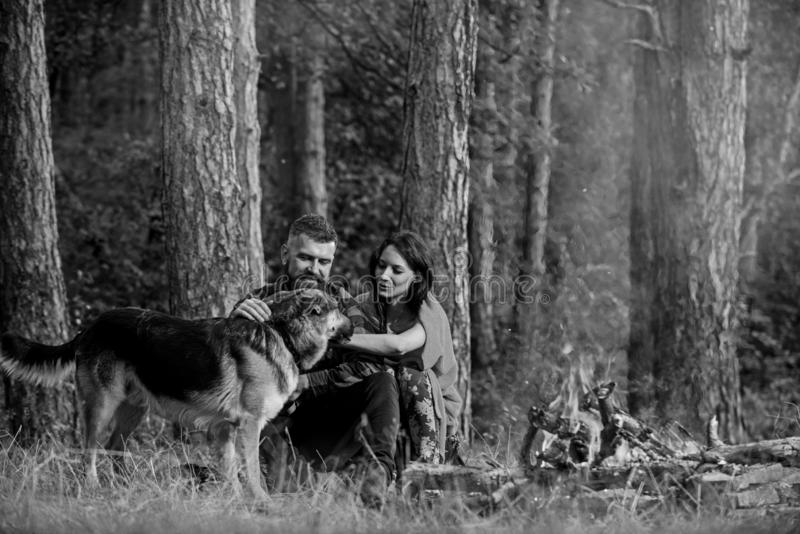Couple pat german shepherd dog near bonfire, nature background. Woman, men and dog on vacation, hiking. Couple in love or young happy family spend time royalty free stock photography