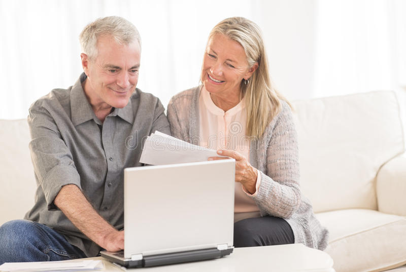 Couple Paying Bills Through Laptop At Home. Happy senior couple paying bills through laptop at home stock photo