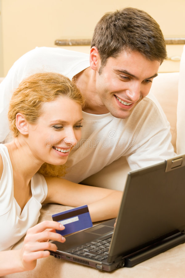 Couple paying by credit card. Happy couple paying by credit card in shop stock photos