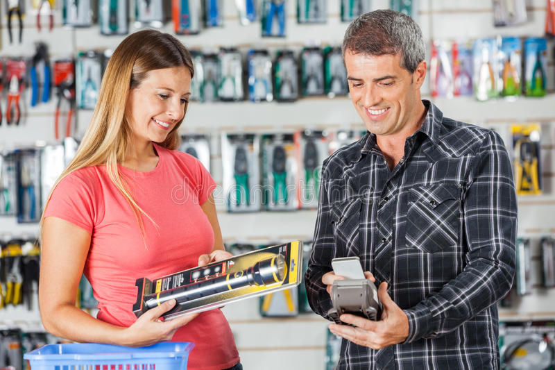 Couple Paying For Flashlight Through Smartphone In. Smiling men and women paying for flashlight through smartphone in hardware store royalty free stock photography