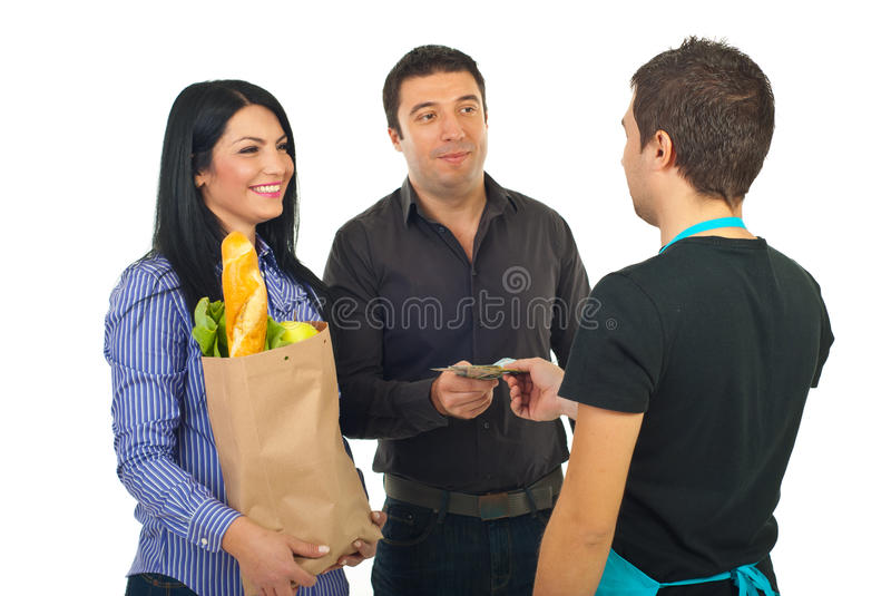 Couple paying with money at supermarket. Happy couple paying their food with money banknotes at supermarket isolated on white background stock photos