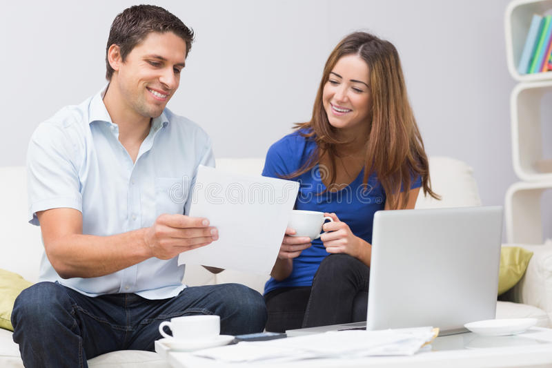 Couple paying their bills online at home. Smiling couple paying their bills online with laptop in living room at home stock images
