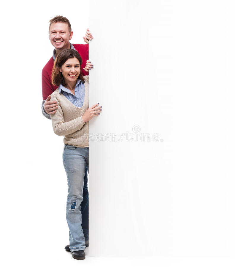 Couple peek out from behind empty blank. Isolated on white background royalty free stock photography
