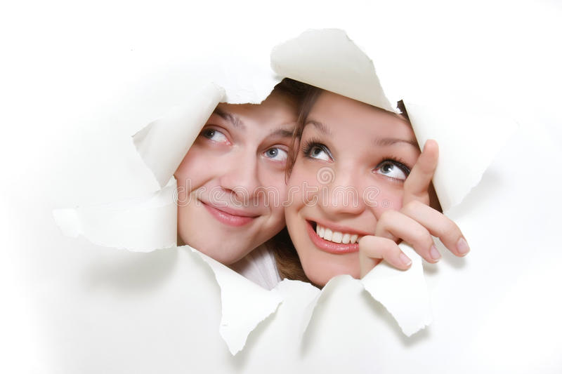 Couple peeping through hole in white paper stock photography