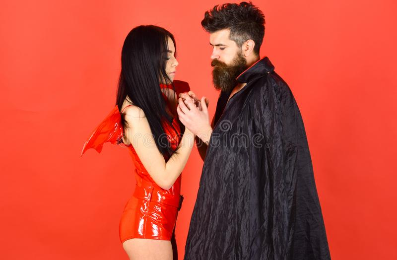 Couple on pensive faces play role game. Devil love concept. Man and woman dressed like vampire, demon, red background. Couple on pensive faces play role game royalty free stock photos