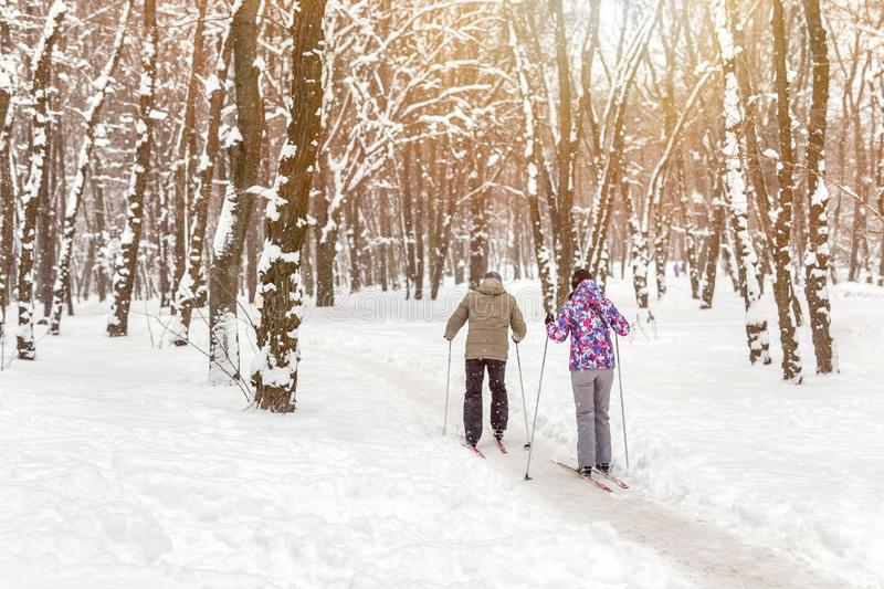 Couple of people enjoying cross-country skiing in city park or forest in winter. Family Sport outdoor activities in winter season stock photo