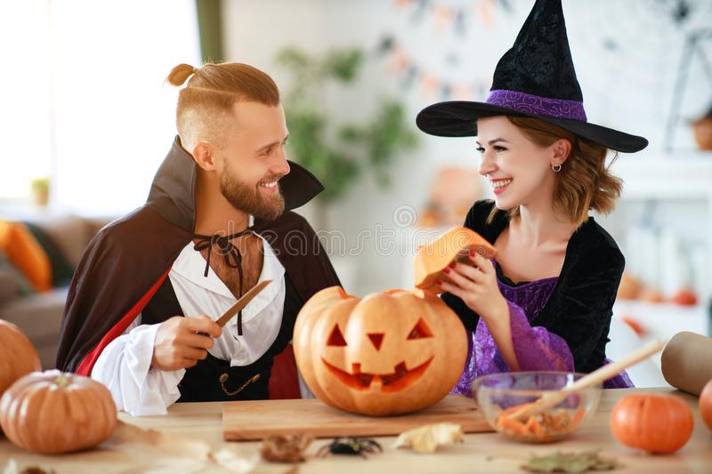 Couple of people are preparing for Halloween in costumes of witch and vampire with pumpkins royalty free stock photo