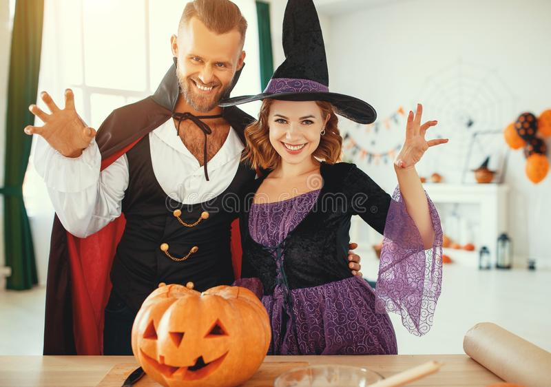 Couple of people are preparing for Halloween in costumes of witch and vampire with pumpkins. Couple of people are preparing for Halloween in costumes of a witch royalty free stock photos