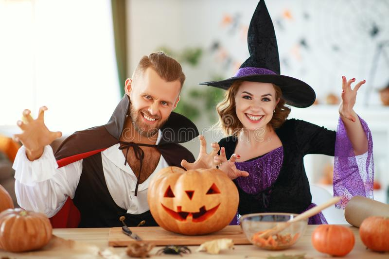 Couple of people are preparing for Halloween in costumes of witch and vampire with pumpkins stock photography