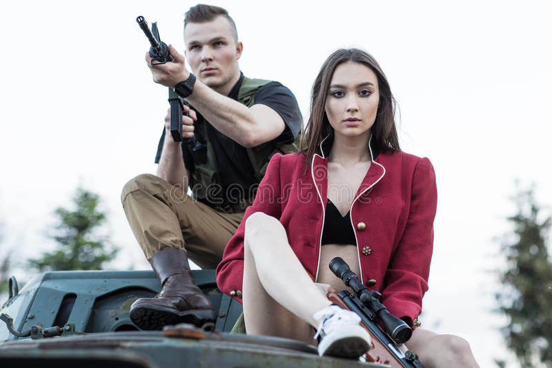 Couple of people sitting on the tank with the gun. Couple of people sitting on the tank with the gun royalty free stock photos