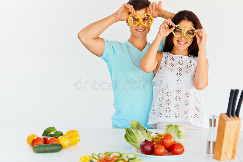 Couple with pepper slices smiling at the camera. Vegetables for royalty free stock image
