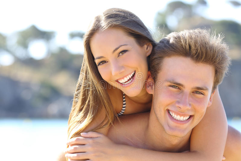 Couple with perfect smile posing on the beach. Happy couple with perfect smile and white teeth posing on the beach looking at camera