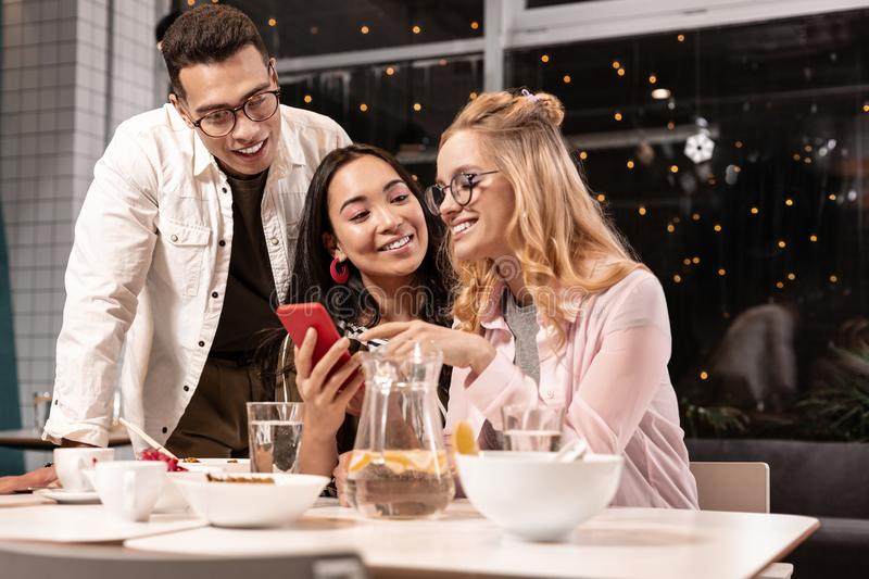 Couple persuading his female friend to write message to guy she liking. Make a step. Pleasant multiracial couple persuading his female attractive friend to stock photo
