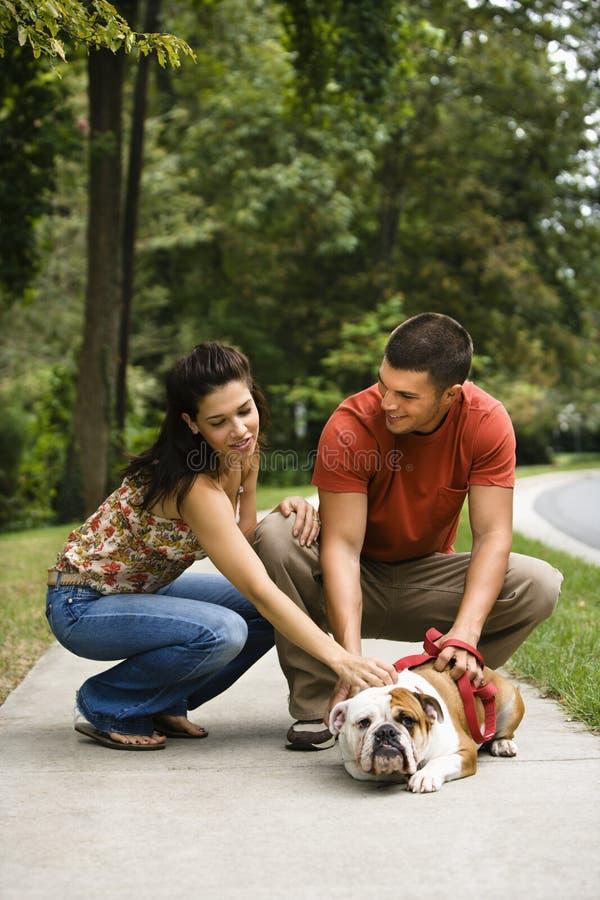 Couple petting dog. royalty free stock images