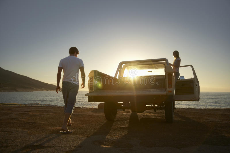 Couple By Pick-Up Truck Parked On Beach. Full length of young couple by pick-up truck parked on beach royalty free stock photography