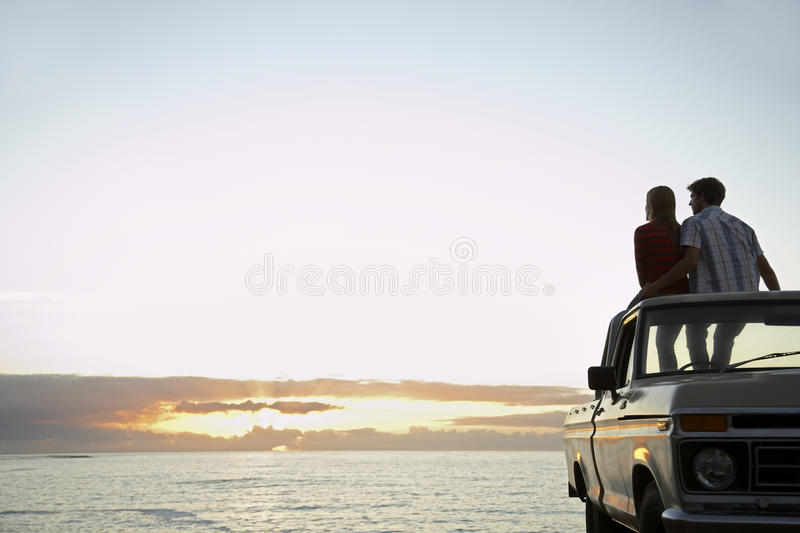Couple On Pick-Up Truck Parked In Front Of Ocean. Rear view of young couple on pick-up truck parked in front of ocean enjoying sunset stock photo