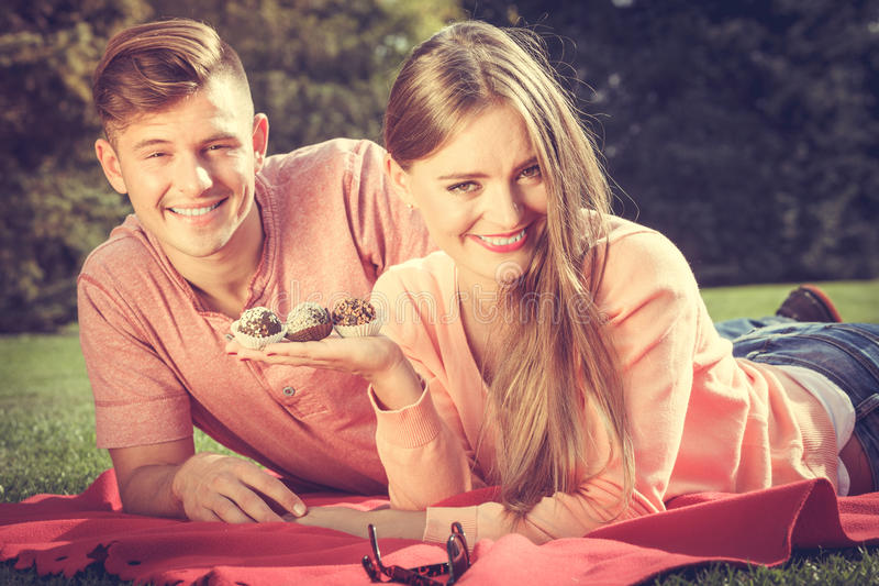 Couple on picnic date outdoor. Love food and happiness. Smiling joyful cute couple on picnic in garden park. Happy lovers dating on fresh air royalty free stock image