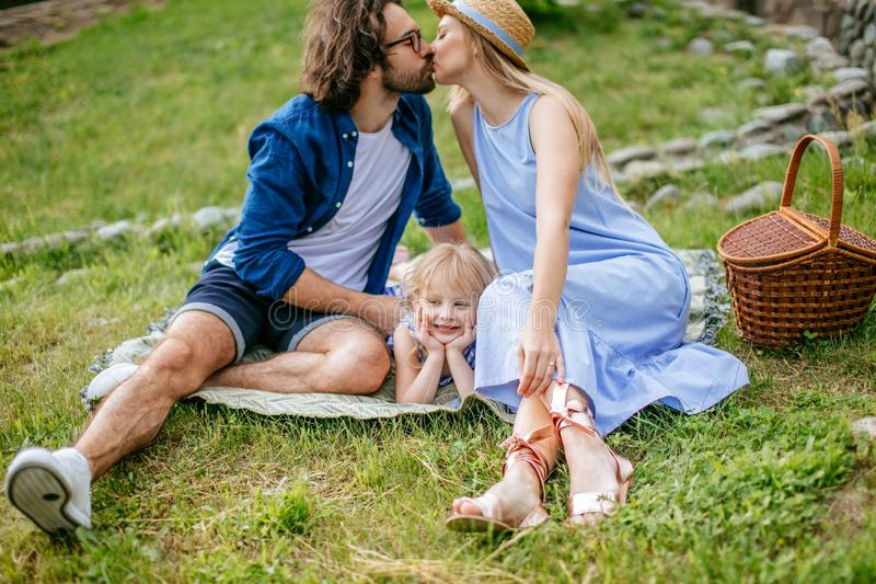 Couple on picnic in field on sunny summer day enjoying and resting. kissing and have fun royalty free stock photography