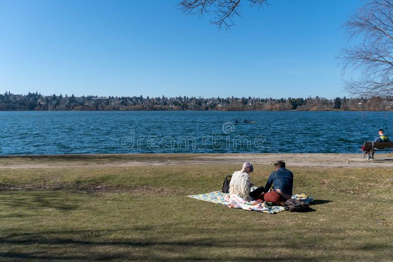 Couple picnic in Greenlake. Seattle, Washington - 2019-03-17 - Couple having a picnic, men reading in a bench and other people canoeing in Greenlake as Spring stock image