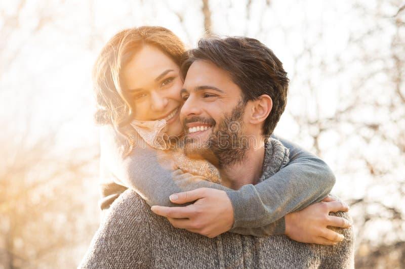 Couple piggyback. Closeup of smiling men carrying women piggyback outdoor stock photography