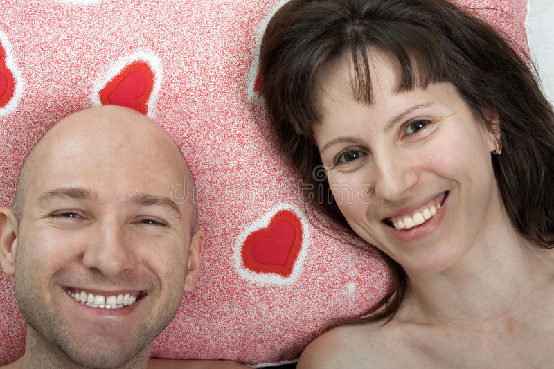 Couple on pillow. Adult couple valentines day red love heart pillow royalty free stock image