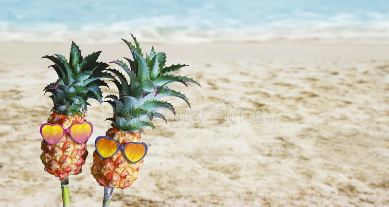 Couple pineapples with sunglasses on sand at the beach. Hello summer concept royalty free stock photo