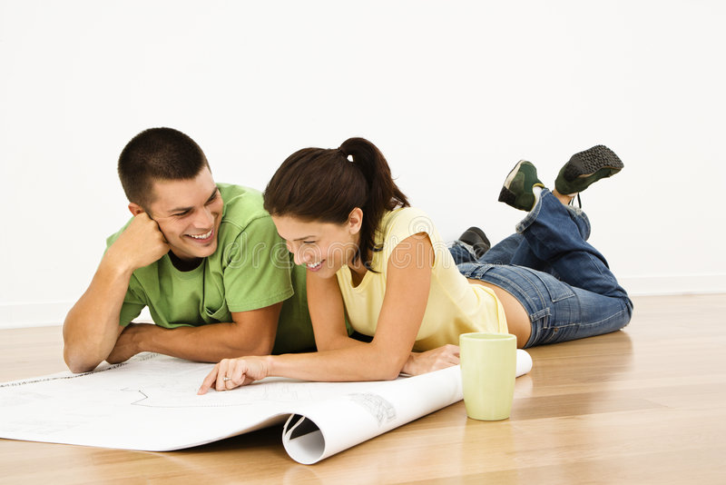 Couple planning future. Attractive young adult couple lying on home floor with coffee cups smiling and looking at blueprints stock photos