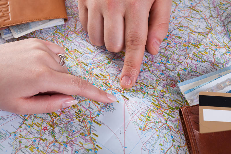 Couple planning travel to Venice, Italy. Couple planning trip to Venice, Italy, pointing on this city on map. Travel background with accessories stock image