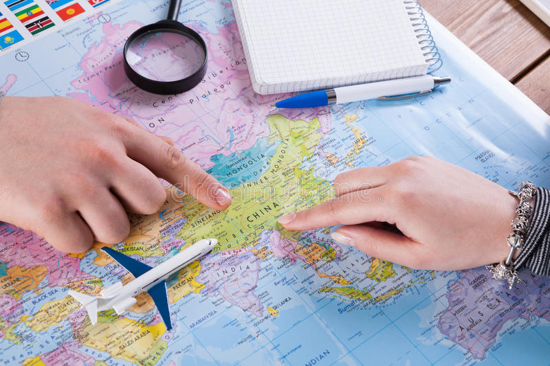 Couple planning trip to China, point on map stock photos