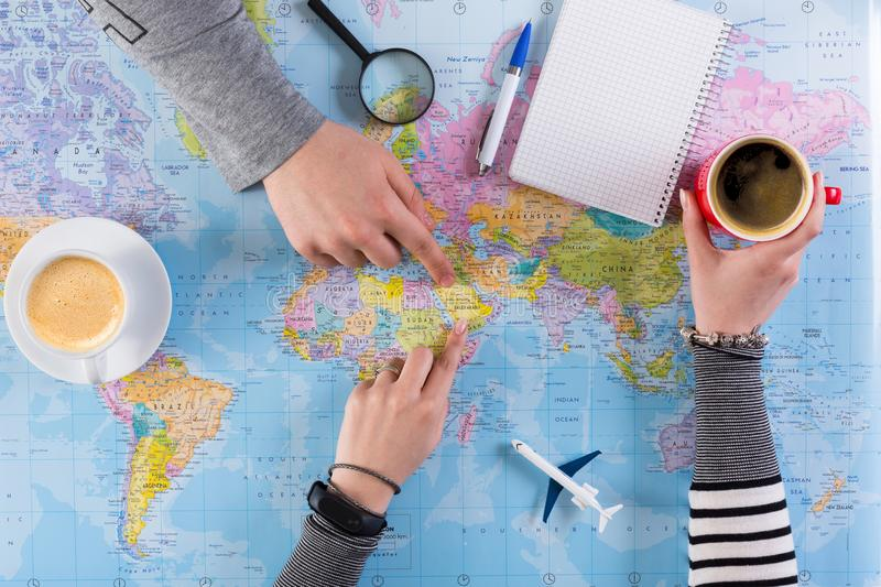 Couple planning trip to Saudi Arabia, point on map stock images