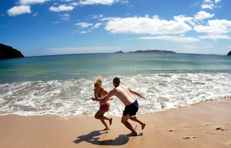 Couple play on empty beach in New Zealand royalty free stock photos