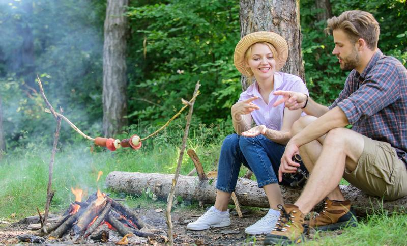 Couple play rock paper scissors hand game. Couple tourists throwing their gesture while sit log near bonfire. Hand stock photography