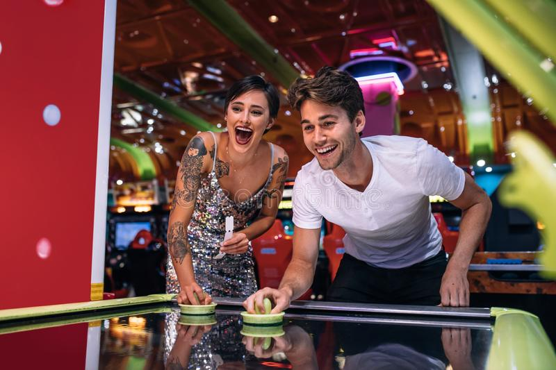 Happy couple playing coin operated air hockey game at a gaming p. Couple playing air hockey game holding strikers at a gaming parlour. Excited men and women royalty free stock photography