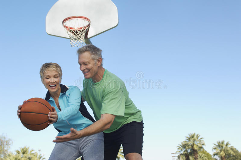 Couple Playing Basketball. Happy Caucasian couple playing basketball at outdoor court stock photo