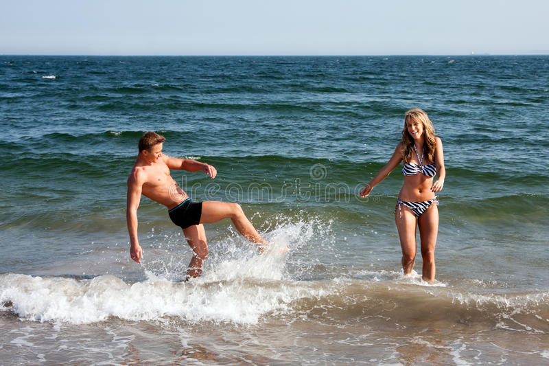 Couple playing in beach water. Beautiful young couple playing in the ocean at the beach splashing water, heaving fun on a summer day