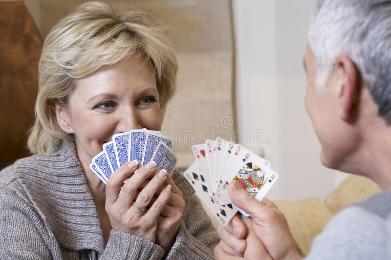 Couple Playing Cards At Home. Happy middle aged couple playing cards at home royalty free stock photography