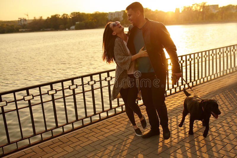 Couple playing with dog in park at sunset stock image