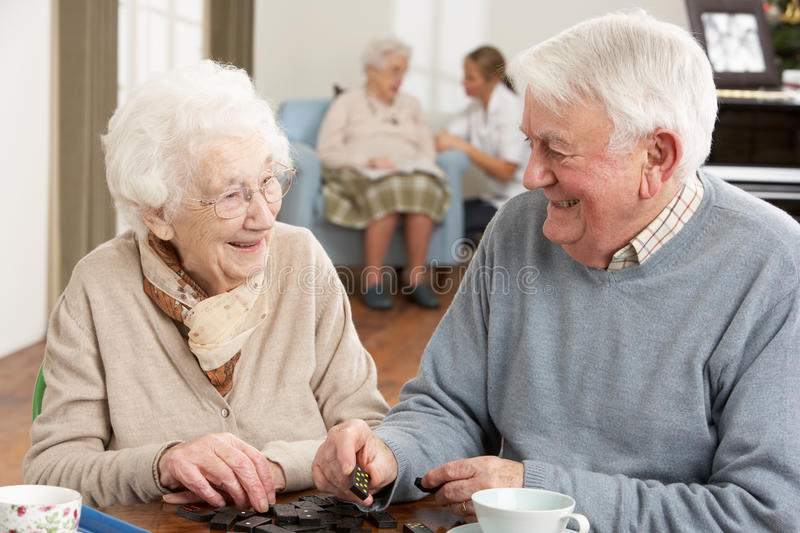 Couple Playing Dominoes At Day Care Centre. Having fun royalty free stock photography